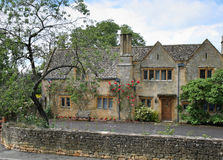 Traditional Stone Medieval English Village House. And garden with climbing Roses on the wall Stock Photo