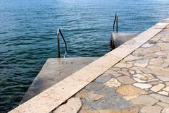 Traditional stone pier leading to two smaller concrete piers with inox handrails for easier entrance and clear blue sea in. Background royalty free stock photography