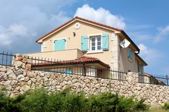 Traditional stone wall with wrought iron fence on top in front of modern Mediterranean villa with new facade and open blue wooden. Window blinds surrounded with stock photos