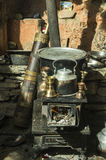 Traditional stove and utstensiles. Traditional stove from Mustang with churn, pan and ceremonial objects. Himalaya. Vertical Royalty Free Stock Photos