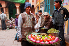 Traditional street food seller presents a dish for everybody and passers-by people Royalty Free Stock Photo