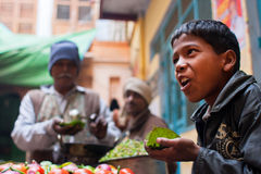 Traditional street food seller presents a dish for everybody and passers-by people Royalty Free Stock Photos