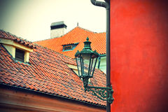 Traditional street lamp and the tiled roofs of Prague Stock Photography