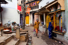 Traditional street life with a sellers, a praying woman and passers-by people. VARANASI, INDIA: Traditional street life with a sellers, a praying woman and Royalty Free Stock Photos