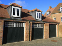 Traditional style garages with wooden doors and Dormer windows. New housing estate in Swindon, Wiltshire, UK. Rather than having houses built in the same style Royalty Free Stock Photography
