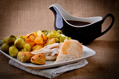 Traditional Sunday dinner with gravy boat. Royalty Free Stock Image