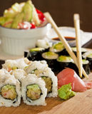 Traditional Sushi Dinner Setting. A closeup on sushi rolls in a take out container with chopsticks and regular wasabi and ginger garnish Royalty Free Stock Images