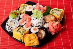 Traditional sushi and rolls. Seafood, Traditional sushi and rolls on the black plate on a red bamboo napkin Stock Images