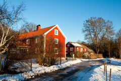 Traditional Swedish houses in winter snow. Traditional red painted Swedish houses in wintry landscape illuminated in a shaft of sunlight surrounded with bare Stock Image