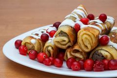Traditional sweet rolled pancakes with poppy seeds on the plate Stock Photos