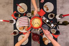 Swiss cheese fondue. Traditional swiss cheese fondue in a red pot on concrete dining table stock photography