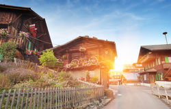 Traditional Swiss country houses. With decorations in Alps at sunset Stock Image