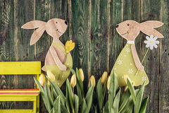 Traditional symbol of spring season like yellow tulips and bunny on wooden background, happy easter time Royalty Free Stock Photos