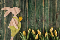 Traditional symbol of spring season like yellow tulips and bunny on wooden background, happy easter time Stock Photos