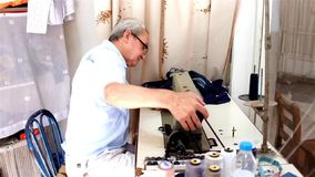 Traditional tailor. Traditional local tailor sews cloths with his sewing machine in his  workshop in Akcay, coastal town on Aegean coast in Turkey stock footage