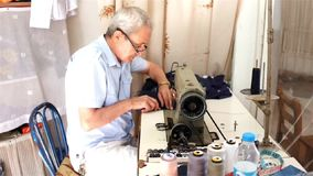 Traditional tailor. Traditional local tailor sews cloths with his sewing machine in his  workshop in Akcay, coastal town on Aegean coast in Turkey stock video footage