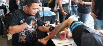 Traditional tattoo artwork at MBK Center Tattoo Fest 2018. BANGKOK, THAILAND - OCTOBER 28, 2018: A Thai artist creates a tattoo on customer`s leg at MBK Center royalty free stock photography