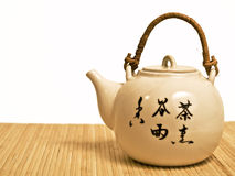Traditional tea-pot. Traditiona japanese teapot on a bamboo tablecloth royalty free stock photo