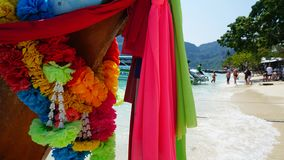 Traditional Thai boat. Colorful bright ribbons and flowers. Background active people. The nose of the boat. Blue water and white sand. Heavenly beach.Travel to royalty free stock photography