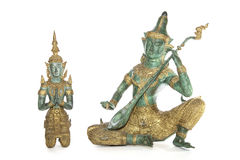 Traditional Thai bronze statues isolated against a white background. Traditional Thai bronze statues of a temple guardian and musician isolated against a white stock photo