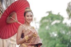 Traditional Thai dresss. Beautiful women wearing a traditional Thai cloth as a wedding dress holding a red umbrella outdoor. Traditional Thai dress. Beautiful royalty free stock images