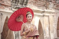 Traditional Thai dress. Beautiful women wearing a traditional Thai cloth as a wedding dress holding a red umbrella outdoor royalty free stock image