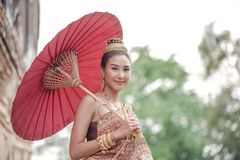 Traditional Thai dress. Beautiful women wearing a traditional Thai cloth as a wedding dress holding a red umbrella outdoor. Traditional Thai dress. Beautiful stock images