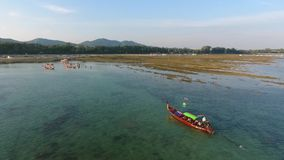 Traditional thai long-tail boat sailing in blue sea in low tide. HD aerial shot. Phuket, Thailand. stock footage