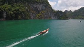 Traditional Thai Long Tail Boat Sailing with Tourists at Cheow Lan Lake. Surat Thani Province, Thailand. Aerial HD. Aerial: Traditional Thai Long Tail Boat stock footage