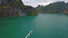 Traditional Thai long tail boat sailing with tourists at Cheow Lan Lake. Surat Thani Province, Thailand. Aerial HD. stock video footage