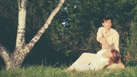 Traditional Thai Massage Outdoor. Healing system with acupressure, Indian Ayurvedic principles, assisted yoga postures. Man and woman in the park. The masseur stock footage