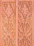 Traditional Thai pattern is carved on the red wooden door. Traditional Thai pattern is carved on the red wooden door of the Thai church in the temple Royalty Free Stock Image