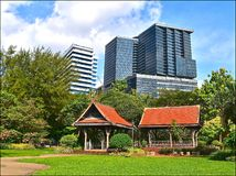 Traditional Thai sala and modern office buildings stock photo