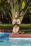 Traditional Thai sculpture and swimming pool in tropical garden. Thailand Stock Photography