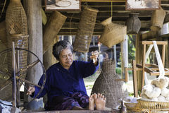 Traditional thai silk cotton spinning wheel. Old lady working on traditional thai silk cotton spinning wheel with bamboo basketwork in background Stock Image