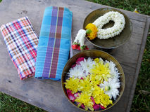 Traditional thai in Songkran day at Thailand. Traditional thai in Songkran day bring garland and petal flowers on water in brass bowl with loincloth by giving Stock Photos