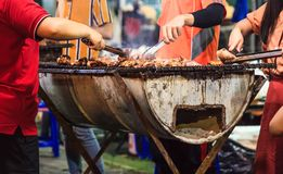 Traditional Thai Street Food, Beef barbecue grill on outdoor fireplace for roasting meat, cooked over open flame or live coal,. Basting with seasoned sauce royalty free stock photos