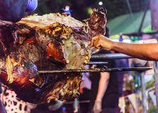 Traditional Thai Street Food, Beef barbecue grill on outdoor fireplace for roasting meat, cooked over open flame or live coal,. Basting with seasoned sauce stock image