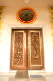 Traditional Thai style door carving and painting art at the temple. Royalty Free Stock Image