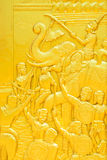 Traditional Thai style golden wood carving about ancient war on. Temple door Royalty Free Stock Photo