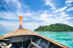 Traditional Thai Wooden Longtail Boat Ride. Traditional Thai wooden longtail boat heads toward the tropical Andaman shores of Bamboo Island, a popular day trip stock photo