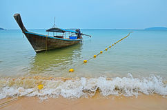 Traditional Thailand old long tail boat in transparent water Royalty Free Stock Photo