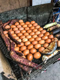 Traditional Thailand Street Food: Grilled/Roasted chicken eggs, sweet taros, mackerel fish and corn on the charcoal grill stove. On the mobile market stall Stock Image