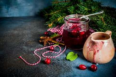 Traditional Thanksgiving Christmas food, homemade cranberry sauce, with mint and fresh berries, dark blue table, with fir tree. And saucer, copy space for text stock photo