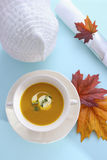 Traditional Thanksgiving pumpkin soup on pale blue table. Stock Photo