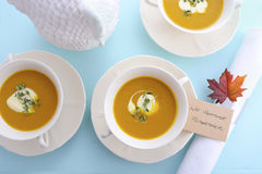 Traditional Thanksgiving pumpkin soup on pale blue table. Royalty Free Stock Images