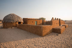 Traditional Thatched Mud Huts. A traditional thatched roof mud hut and home in the Thar desert in Khuri, Rajasthan, India Stock Image