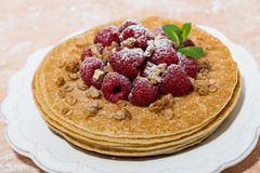 Traditional thin pancakes with fresh raspberries on plate. Closeup horizontal Stock Photo