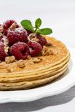 Traditional thin pancakes with fresh raspberries on wooden table. Closeup Stock Photo