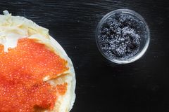 Traditional thin Russian pancakes with red caviar on a dark rustic wooden background stock images
